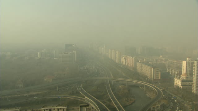 WS HA Network of freeways cutting through city, sky thick with smog / Beijing, China