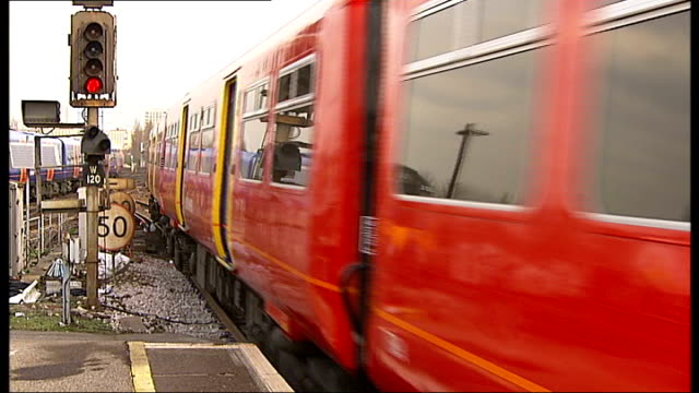 General views of trains along track rail passengers ENGLAND London Clapham Junction EXT Close up of train speeding along past / Close up of SouthWest...