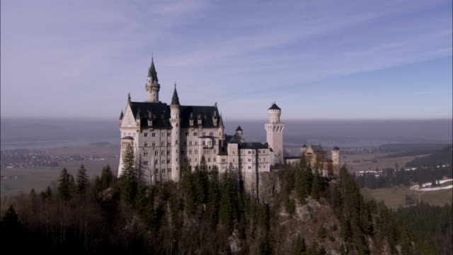 Neuschwanstein Castle overlooks plains from a high promontory. Available in HD.