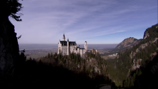 Neuschwanstein Castle sits on a forested hill in Bavaria Germany. Available in HD.