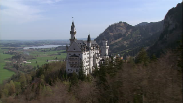 vidéos et rushes de neuschwanstein castle towers over the countryside in bavaria, germany. - château