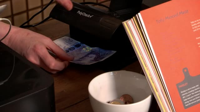 new £20 banknote featuring artist jmw turner 'most secure yet' england london int various shots of customer swiping bank card on card reader at till... - paying stock videos & royalty-free footage