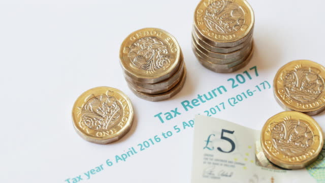 new 2017 one pound coins on uk tax return - 4k - income tax stock videos and b-roll footage
