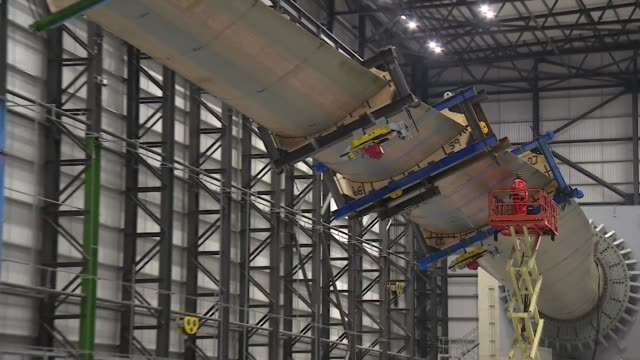 new 88 metre long blade for a wind turbine being tested in a large factory hangar - windmill stock videos & royalty-free footage