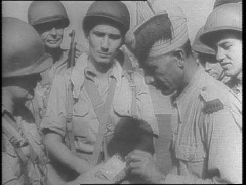 new american expeditionary force arrive in india hitting burma from push / shots of us soldiers carrying equipment and heavy loads from transport... - anno 1943 video stock e b–roll