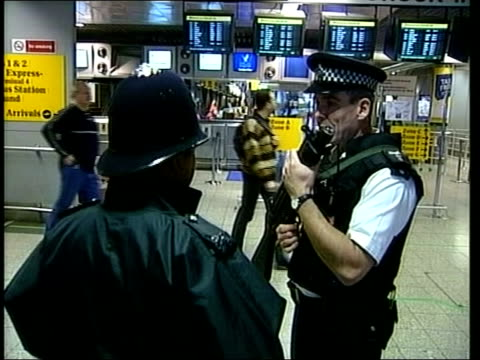 new antiterrorism and relgious hatred laws planned lib london heathrow airport int armed police officer on duty inside airport terminal luggage... - armed police forces stock videos & royalty-free footage