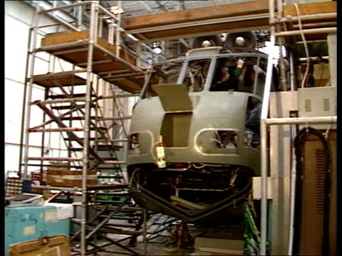 stockvideo's en b-roll-footage met somerset yeovil tcms engineers inside helicopter cockpit pull out to scaffolding around heli tms westland 30 heli others on westland factory floor... - yeovil