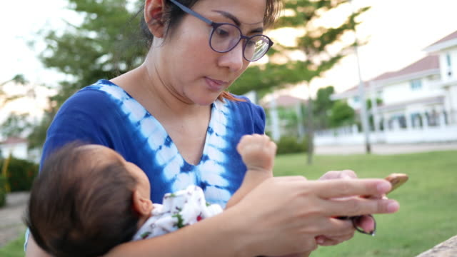 new born baby and mother using mobile phone in the park - information medium stock videos & royalty-free footage