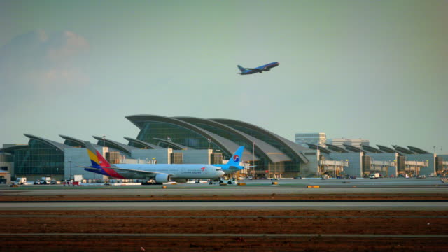 W/S new Bradley International terminal at LAX, Asiana Boeing-777 is towed to gates, airplane climbs on take-off in background