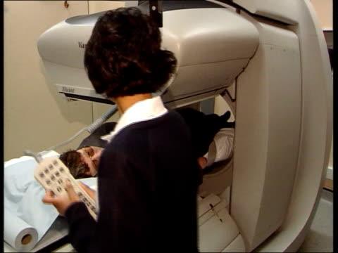 new breast cancer scanning technique england london st bartholomew's sue lumsden on bed on scanning machine as moved into machine scanning equipment... - lymfsystem bildbanksvideor och videomaterial från bakom kulisserna