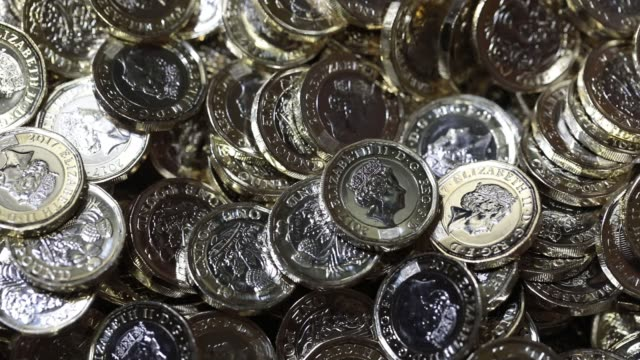 new british one pound coins drop into a container after being produced at the royal mint in llantrisant uk on thursday march 23 a worker operates a... - financial accessory stock videos and b-roll footage