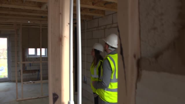 New build housing construction in Bedfordshire ENGLAND Bedfordshire Bedford EXT Couple looking at housing estate under construction including holding...