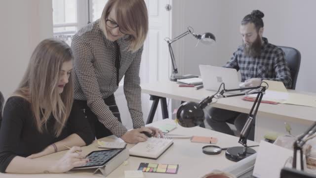 vídeos de stock, filmes e b-roll de equipe de novos negócios: trabalhando juntos no escritório inicialização - coworking space