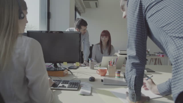 new business team: at work together in the startup office - società video stock e b–roll