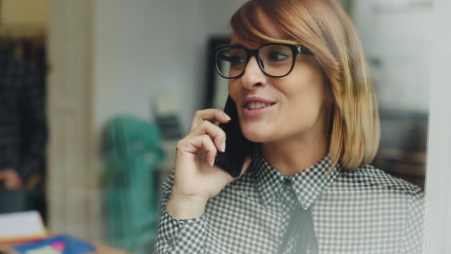 new business team: woman at the phone in studio - usare il telefono video stock e b–roll