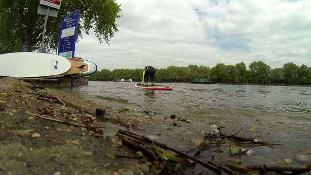 new centre opens in putney; england: london: putney embankment: active 360: ext shots of paddle boarders carrying their boards down to the river... - embankment stock videos & royalty-free footage