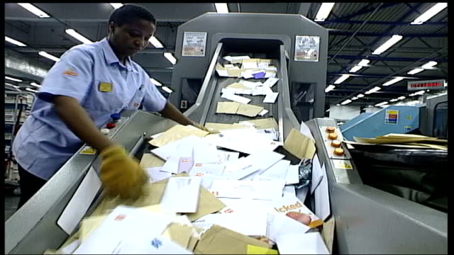 new changes to royal mail postal system: consumer group says customers do not know enough; int postal worker sorting thru letters on a conveyer belt... - ロイヤルメール点の映像素材/bロール