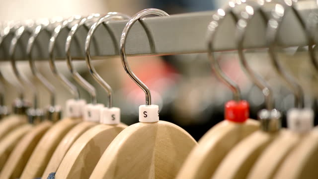 new clothes on hangers in shop - clothing stock videos and b-roll footage