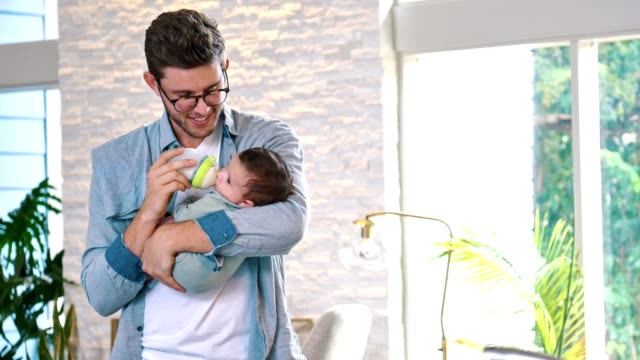 new dad cares for infant son at home - biberon video stock e b–roll