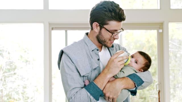 vidéos et rushes de le nouveau papa nourrit le fils en bas âge - nourrir