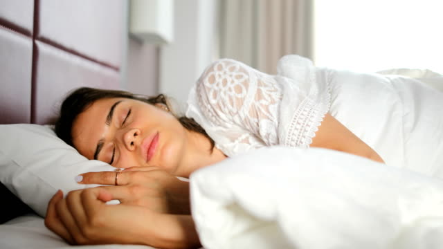 new day.young woman opens her eyes on a sunny morning - ora di andare a letto video stock e b–roll