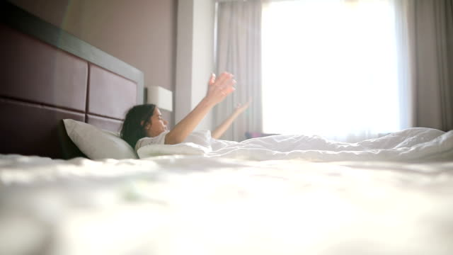 vídeos de stock e filmes b-roll de new day.young woman stretching in bed after wake up - acordar