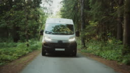 New Delivery Van / Truck Driving Through the Green Woods. Postal Delivery Service. Front View Following Shot