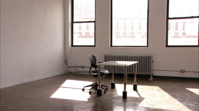 New desk and chair in sunlight in empty loft space