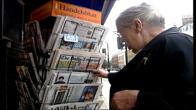 vídeos y material grabado en eventos de stock de new drug helps prevent loss of sight; england: london: ext side view of lydia willie choosing a newspaper from a newspaper stand - new age