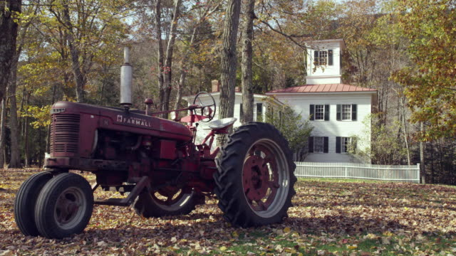 new england farmhouse with rusted tractor fall - farmhouse stock videos & royalty-free footage