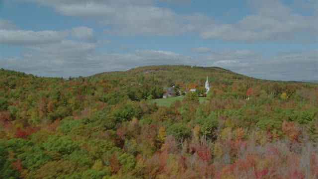 AERIAL New England town + surrounding forests in Autumn