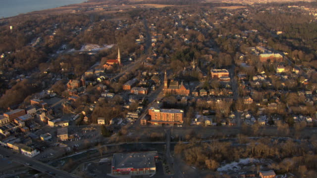 AERIAL New England town with fall foliage and buildings with morning sunlight / United States
