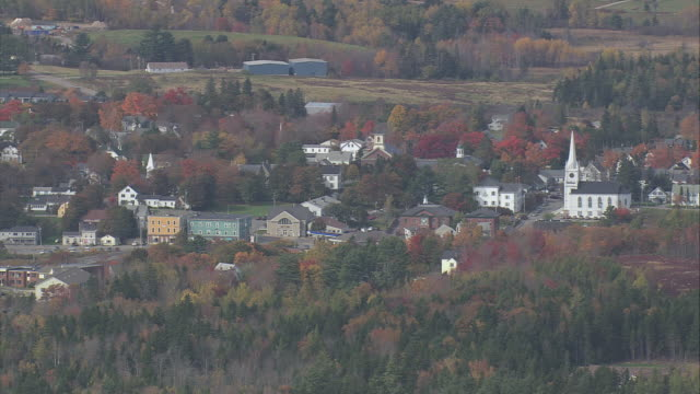 stockvideo's en b-roll-footage met aerial new england town with white church steeple and trees in fall colors / maine, united states - kerktoren