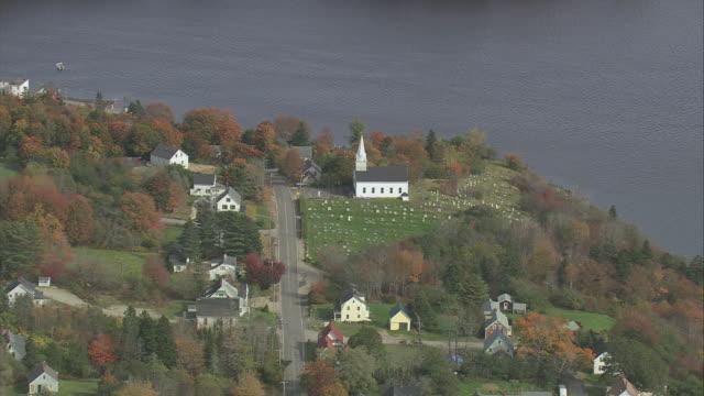 aerial new england village with white church at coastline with trees in fall color / maine, united states - tornspira bildbanksvideor och videomaterial från bakom kulisserna