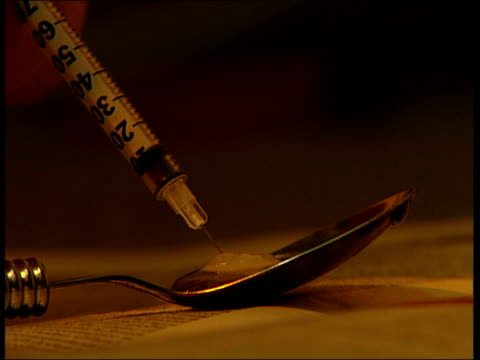 stockvideo's en b-roll-footage met new focus on dealers lib heroin user preparing drugs for injection - injecting heroin