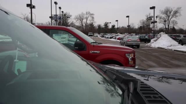 new ford f150 trucks are displayed for sale on the lot at the oxmoor ford dealership in louisville kentucky close up shots of a ford logo on the... - ford marca di veicoli video stock e b–roll