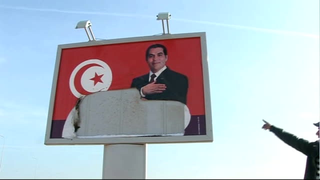 New government announced as protests continue EXT Man throwing handful of dirt at ripped poster of former Tunisian President Ben Ali Demonstrators...