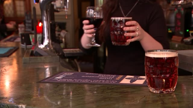 New government guidelines on alcohol consumption Pints of beer and glas sof red wine on bar in pub Pint of beer pulled behind bar Group of people...