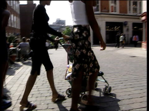 new government measures on teenage mothers lib woman pushing pushchair along street babie pushed along in double buggy - spingere video stock e b–roll