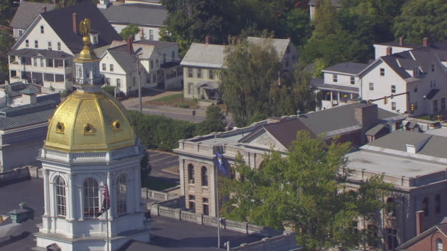 ws zo aerial pov new hampshire flag and american flag waving over new hampshire state house, cityscape / concord, new hampshire, united states - flag stock videos & royalty-free footage