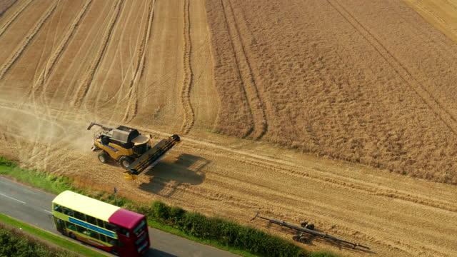 new holand combine harvester & double decker bus, cayton bay, north yorkshire, england - dubbeldäckarbuss bildbanksvideor och videomaterial från bakom kulisserna