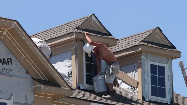 vidéos et rushes de new home construction, a painter paints the peak of a roof - classe ouvrière