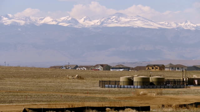 New home construction near oil storage tanks flares snowy Rocky Mountains Weld County Erie Colorado