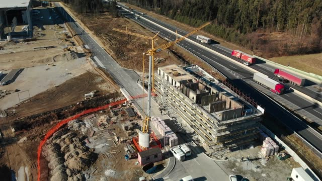 new hotel is being built by the highway - crane construction machinery stock videos & royalty-free footage