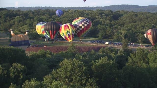 vídeos de stock, filmes e b-roll de new jersey balloon festival hot air balloons float over trees on july 26 2013 in readington new jersey - festa do balão de ar quente