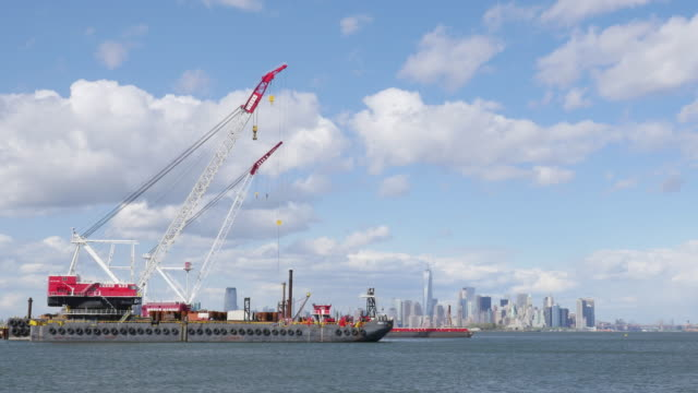 New Jersey construction boat is docked at port and Manhattan buildings are in the background