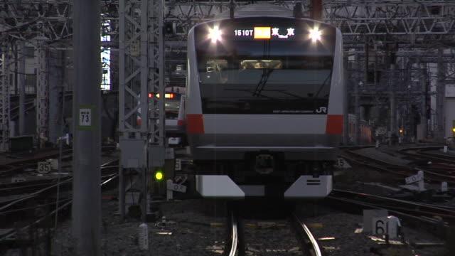 vídeos de stock, filmes e b-roll de ms cu new jr chuo line train approaching to shinjuku train station at dusk / tokyo, japan - indo em direção