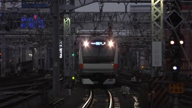 vídeos de stock, filmes e b-roll de ms cu zo new jr chuo line train approaching to shinjuku train station at dusk / tokyo, japan - indo em direção