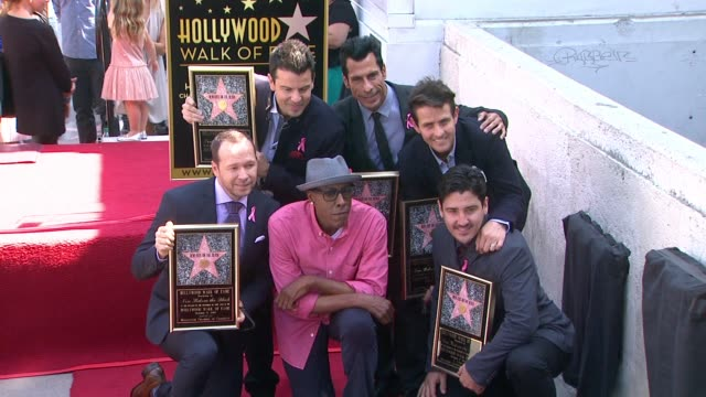 New Kids On The Block posing with plaques and Arsenio Hall at New Kids On The Block honored with star on the Hollywood Walk of Fame in Hollywood CA on