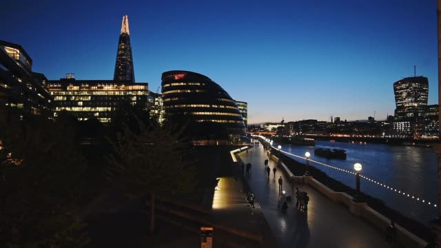new london city hall and tower bridge at night with people walking on the sidewalk. london, england, uk. - wide shot - tourism stock videos & royalty-free footage